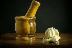 Mortel och mortelstöt med vitlök på en trätabell Arkivfoto