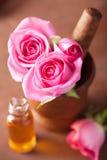 Mortero con el aceite esencial de las flores color de rosa para el aromatherapy Imágenes de archivo libres de regalías