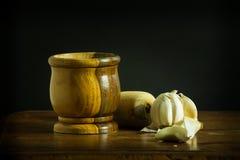 Mortero y maja con ajo en una tabla de madera Foto de archivo
