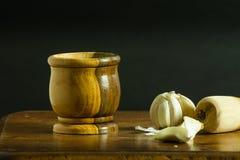 Mortero y maja con ajo en una tabla de madera Fotos de archivo