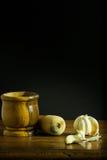 Mortero y maja con ajo en una tabla de madera Imagen de archivo