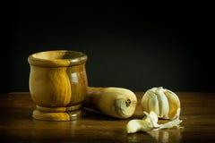 Mortero y maja con ajo en una tabla de madera Fotografía de archivo libre de regalías
