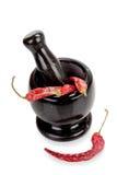 Mortero y maja de mármol negros con la pimienta de chiles rojos aislada en blanco Imagen de archivo libre de regalías