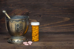 Mortero y maja de RX con las tabletas rosadas con la botella de la prescripción en el fondo de madera Foto de archivo
