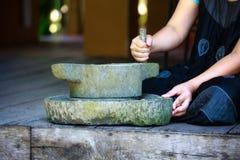 Mortero y mujer de piedra tradicionales foto de archivo libre de regalías