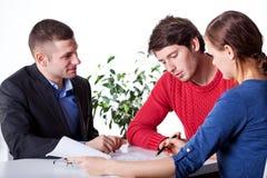Mortgage advisory service. A men and a women signing mortgage papers at advisory service
