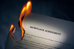 Mortgage Agreement Contract Burning On Fire. Closeup of morgage loan agreement burning. Concept shot of freedom from debts and new beginnings Royalty Free Stock Photo