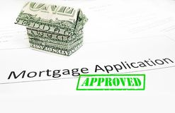 Mortgage app approval. A mortgage application with an origami dollar house and Approval stamp royalty free stock photography