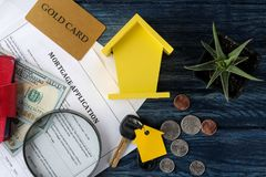 Mortgage application. Key with house keychain and blank and money on a blue wooden table. concept of buying a home. top view royalty free stock image