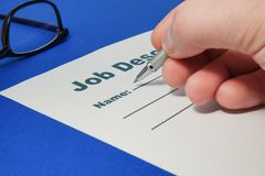 Job Description with Pen and Hand on blue background. Job Description with Hand and Pen on blue background close up stock image