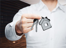 Mortgage concept. Businessman holding key with house keychain in modern interior. Mortgage concept. 3D Rendering Royalty Free Stock Photography
