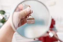 Mortgage concept. Men hand holding key with house keychain. Modern light lobby interior. Real estate, moving home or Stock Photography