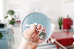 Mortgage concept. Men hand holding key with house keychain. Modern light lobby interior. Real estate, moving home or Stock Photo