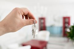 Mortgage concept. Men hand holding key with house keychain. Modern light lobby interior. Real estate, moving home or. Renting property stock images