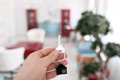 Mortgage concept. Men hand holding key with house keychain. Modern light lobby interior. Real estate, moving home or. Renting property royalty free stock photo