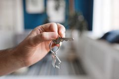 Mortgage concept. Men hand holding key with house shaped keychain. Modern light lobby interior. Real estate, moving home. House key and keychain in the form of stock image