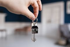 Mortgage concept. Men hand holding key with house shaped keychain. Modern light lobby interior. Real estate, moving home. House key and keychain in the form of stock photography