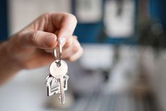 Mortgage concept. Men hand holding key with house shaped keychain. Modern light lobby interior. Real estate, moving home. House key and keychain in the form of royalty free stock photography