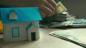 Mortgage concept. Model of house and process of counting money. Real estate loan stock footage