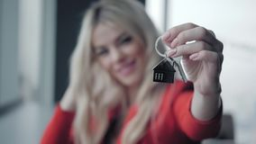 Mortgage concept. Woman in red business suit holding key with house shaped keychain. Modern light lobby interior. Real. Estate, moving home or renting property stock video