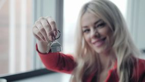 Mortgage concept. Woman in red business suit holding key with house shaped keychain. Modern light lobby interior. Real. Estate, moving home or renting property stock video footage
