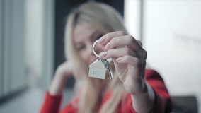 Mortgage concept. Woman in red business suit holding key with house shaped keychain. Modern light lobby interior. Real. Estate, moving home or renting property stock footage