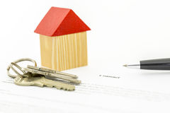 Mortgage contract. Closeup of wooden toy house and keys on mortgage contract Royalty Free Stock Photos