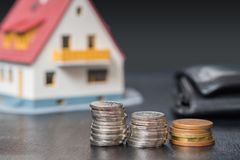 Mortgage copncept. Money and coins in front of a house Royalty Free Stock Photo
