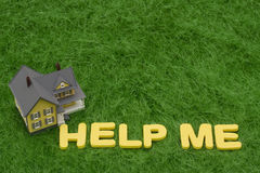 Mortgage Crisis. House with the words help me on grass. mortgage crisis Royalty Free Stock Photo