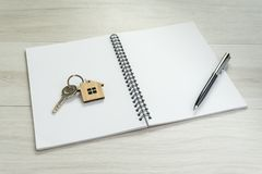 Mortgage, debt or property loan, white blank page of notepad and pen on the right hand side, key with house key chain on the left. On light grey wooden table royalty free stock image