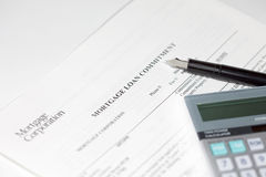Mortgage document, pen and calculator. A pen and calculator sitting on a mortgage loan commitment document Stock Photos