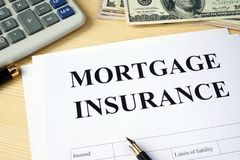 Mortgage insurance policy on a desk. Mortgage insurance policy on a wooden desk Stock Images