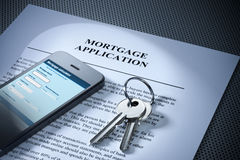 Mortgage Loan Keys Cell Phone. A still-life with a home loan mortgage application, home loan calculator on smartphone and keys Stock Photography