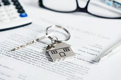 Mortgage loan agreement application with house shaped keyring. Calculator and pen stock images