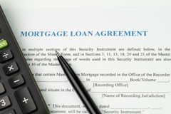 Mortgage loan agreement sign contract concept, pen with calculat. Or on mortgage form or contract, long term debt or real estate investment royalty free stock image