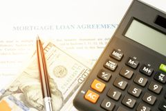 Mortgage loan agreement sign contract concept, pen on US dollar. Banknotes with calculator on mortgage form or contract, long term debt or real estate stock images