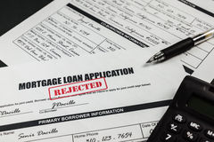 Mortgage Loan Application Rejected 005. Filled-up mortgage loan application form with rejected stamp, calculator and a black pen royalty free stock photography