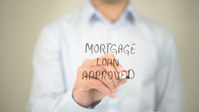 Mortgage Loan Approved , Man writing on transparent screen. High quality royalty free stock photo
