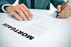 Mortgage loan contract. Man wearing a suit sitting in a table signing mortgage loan contract Stock Photos