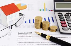 Mortgage loans concept with close up business fountain pen and money coins stack and calculator and paper house and eyeglasses on. Loans request form document royalty free stock photos