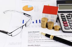Mortgage loans concept with close up or Fountain pen and coins stack and paper house and calculator and glasses on loans request f. Orm stock photo