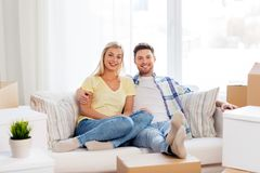 Happy couple with boxes moving to new home. Mortgage, moving and real estate concept - happy couple with boxes resting on sofa at new home royalty free stock photography
