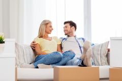 Happy couple with boxes moving to new home. Mortgage, moving and real estate concept - happy couple with boxes resting on sofa at new home royalty free stock image