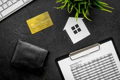 Mortgage payment schedule near bank card and wallet on black background top view.  Stock Image