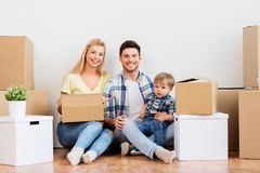 Happy family with boxes moving to new home. Mortgage, people, family and real estate concept - happy mother, father and little son with cardboard boxes moving to stock photo