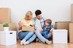 Happy family with boxes moving to new home. Mortgage, people, family and real estate concept - happy mother, father and little son with cardboard boxes moving to royalty free stock photos