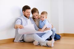 Happy family with blueprint moving to new home. Mortgage, people, housing and real estate concept - happy family with blueprint or house project moving to new Royalty Free Stock Photos