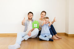 Family with green house showing thumbs up at home. Mortgage, people, housing and real estate concept - happy family with green paper house moving to new home and Royalty Free Stock Photo