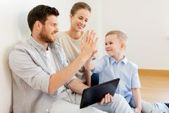 Family with tablet pc at new home making high five Stock Photo