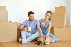 Happy couple with boxes and dog moving to new home Royalty Free Stock Image